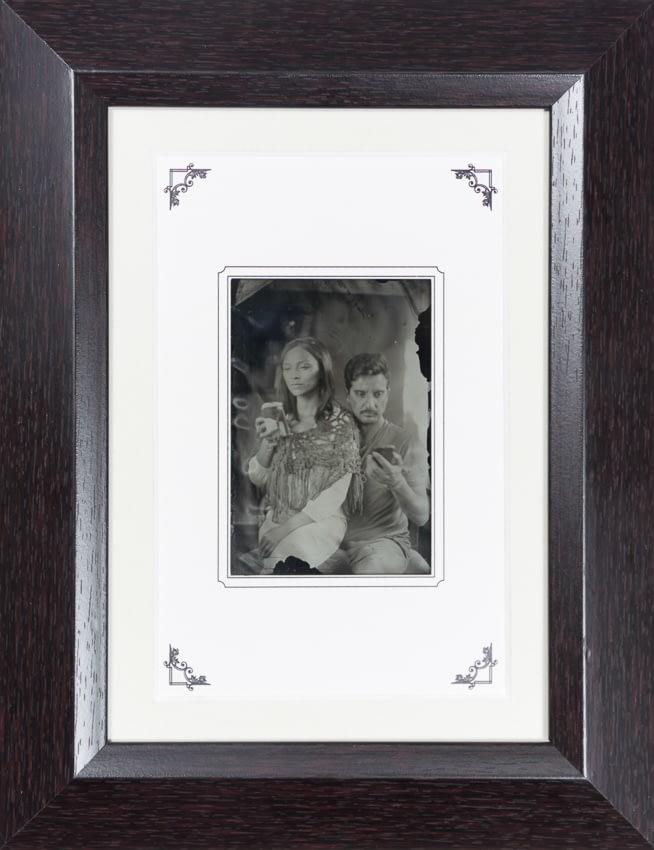 Retrato en ambrotipo de pareja mirando sus celulares