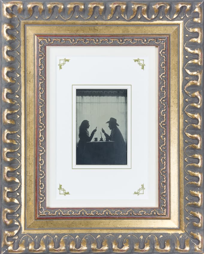 retrato en ambrtipo de pareja desayunando mientras mira sus celulares